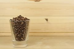 Glass with coffee beans standing on a wooden shelf. Stock Images
