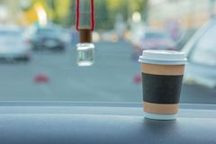 A glass of coffee, on a blurry background of a car air freshener stock images