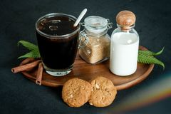 Glass of coffee with brown sugar and milk. Cookies and cinnamon stock photos