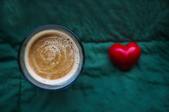 Glass of coffee on the green textile background. Top view. Red heart is near the glass of coffee. Copy space Royalty Free Stock Photos