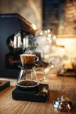 Glass coffee pot with steam on wooden counter Stock Images