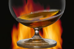 Glass with cognac on a background a fire Stock Photos