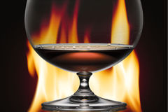 Glass with cognac on a background a fire Stock Photography