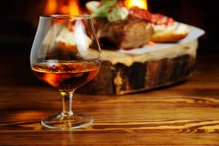 Glass of cognac on the background  a meat dish Stock Photo