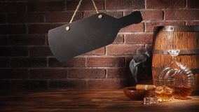 Glass of cognac with barrel on brick backgroun.  Stock Image
