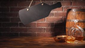Glass of cognac with barrel on brick backgroun.  Royalty Free Stock Photos