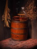 Glass of cognac with barrel in cozy cellar.  Stock Image