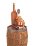 Glass of cognac with barrel on white backgroun Royalty Free Stock Photos