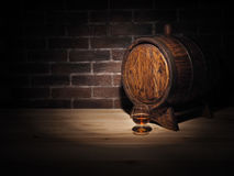 Glass of cognac with barrel on wooden table.  Royalty Free Stock Photo