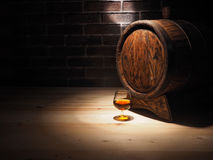 Glass of cognac with barrel on wooden table.  Stock Photos
