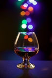 Glass of cognac on bokeh background. Glass with alcohol on the table in the dark Stock Image