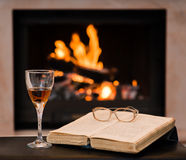 Glass of cognac and book by the fireplace Royalty Free Stock Photos