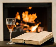Glass of cognac and book by the fireplace Stock Images