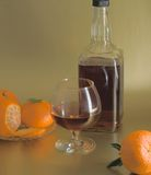 Glass of cognac, bottle and clementines Royalty Free Stock Image