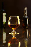 Glass of cognac, brandy or whiscy on black mirror table. bottles in a bar on the background Royalty Free Stock Photos