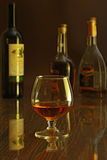 Glass of cognac, brandy or whiscy on mirror table. bottles in a bar on the background Royalty Free Stock Image