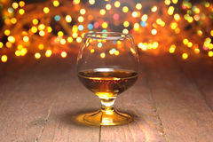 Glass of cognac, brandy or whiscy on mirror table. bottles in a bar on the background Stock Image
