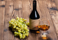 Glass of cognac and bunch of grapes Stock Photo