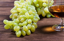 Glass of cognac and bunch of grapes Royalty Free Stock Images