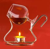 Glass with cognac and candles Royalty Free Stock Images