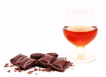 Glass with cognac and chocolate bars stack isolated on a white Royalty Free Stock Image