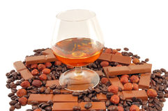 Glass with cognac with chocolate, coffee and nuts Royalty Free Stock Images