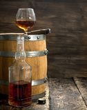 Glass of cognac with a cigar on a barrel. On a wooden background Stock Photo
