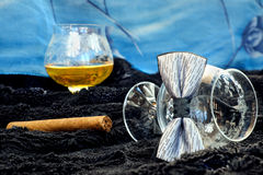Glass of cognac with a cigar on a black velvet with a blue backdrop Stock Photography