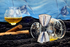Glass of cognac with a cigar on a black velvet with a blue backdrop Stock Photo