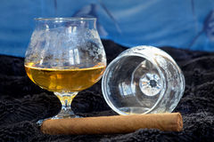 Glass of cognac with a cigar on a black velvet with a blue backdrop Royalty Free Stock Photo