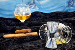 Glass of cognac with a cigar, bow tie on a black velvet with a blue backdrop Royalty Free Stock Photo