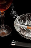 Glass of cognac and cigarette Royalty Free Stock Images