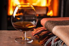 A glass of cognac in front of fireplace Royalty Free Stock Photos