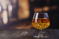 Glass of Cognac with ice cubes royalty free stock photography