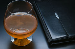 Glass with cognac and the leather notebook. Glass with cognac and a leather purse on a black background Stock Images