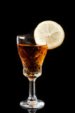 Glass of cognac with lemon Stock Photography