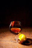 Glass of cognac with lemon on wooden background Stock Photos