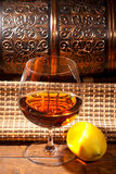 Glass of cognac with lemon on wooden background Royalty Free Stock Photos