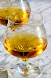 Glass of cognac on a marble table Stock Images