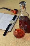 Glass with cognac and notebook Royalty Free Stock Images