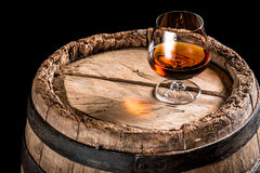 Glass of cognac on old oak barrel royalty free stock photo