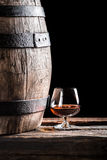 Glass of cognac and old oak barrel Royalty Free Stock Image