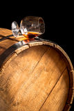 Glass of cognac on the old wooden barrel Stock Photos