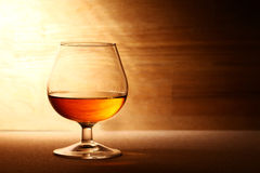 Glass of cognac over wooden surface Royalty Free Stock Image
