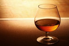 Glass of cognac over wooden surface Royalty Free Stock Images