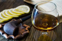 A glass of cognac, a pipe in the ashtray, sliced lemon on a glass plate and an old book on textured oak table. Copy past Stock Photos