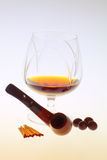 Glass of cognac with a pipe Royalty Free Stock Photos