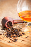 Glass of cognac and pipe with tobacco Stock Image