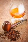 Glass of cognac and pipe with tobacco Royalty Free Stock Images