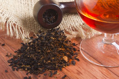 Glass of cognac and pipe with tobacco Royalty Free Stock Photos